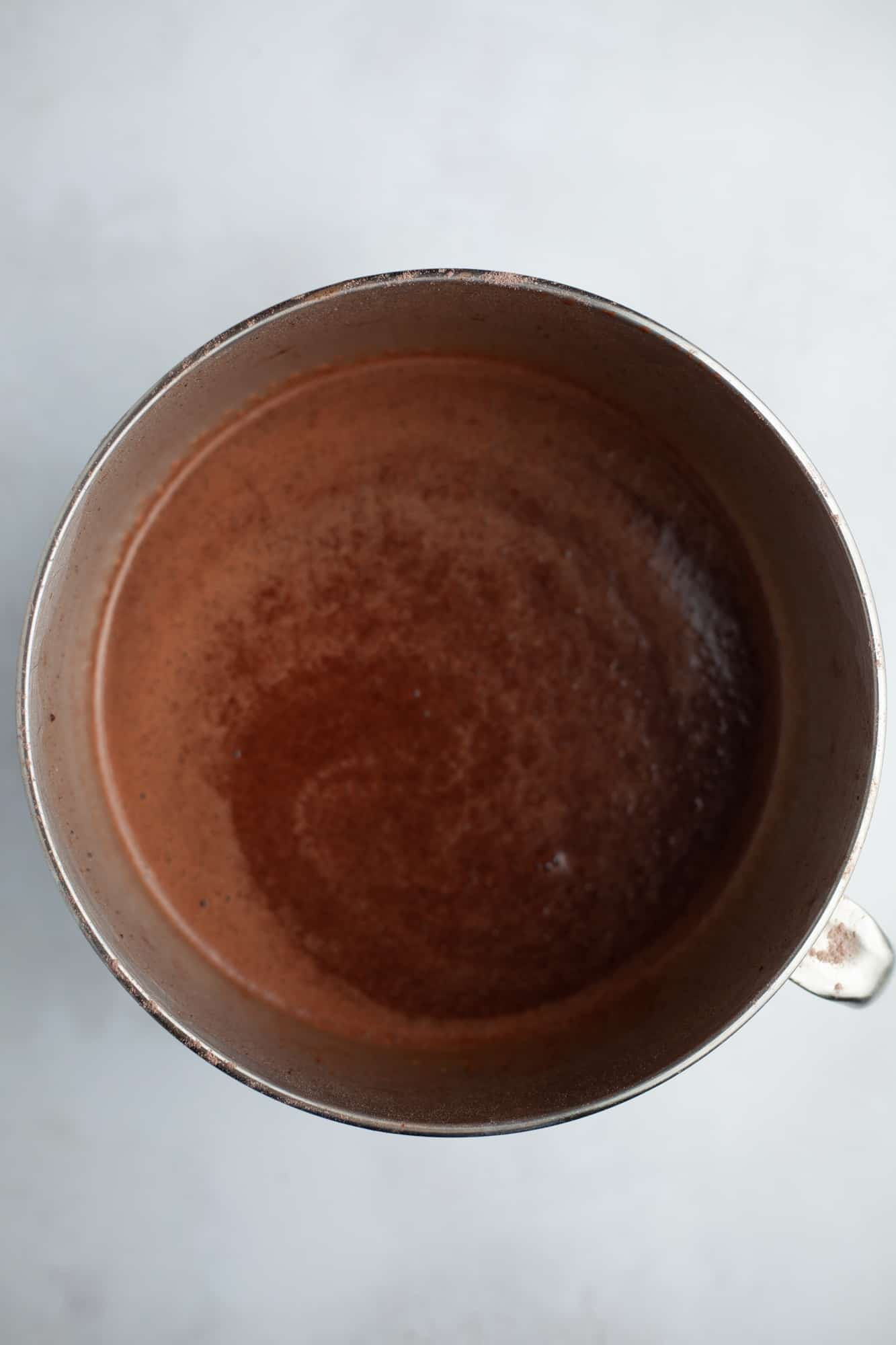 A large silver mixing bowl with chocolate cake batter in it