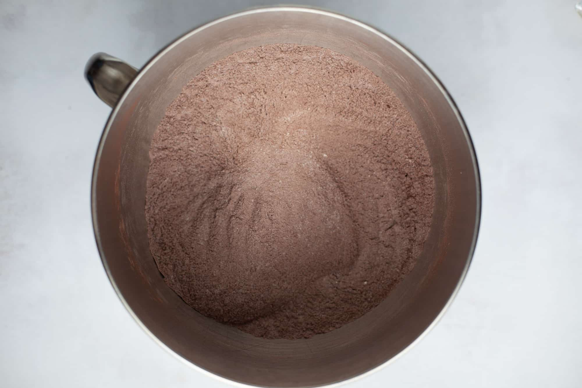 A large silver mixing bowl with a dry cocoa powder and flour mixture