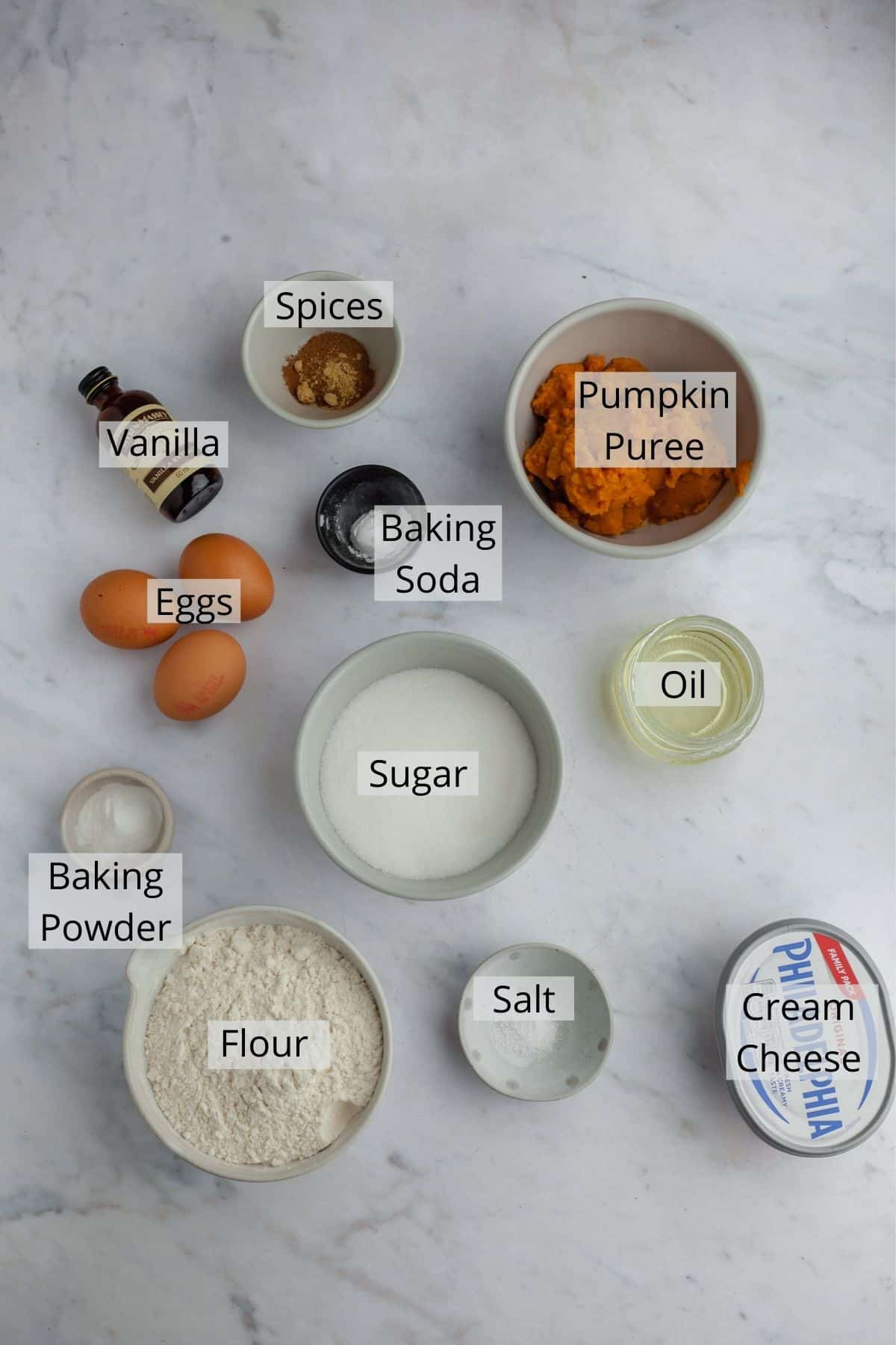 ingredients for cheesecake pumpkin bread weighed out in small bowls on a marble countertop
