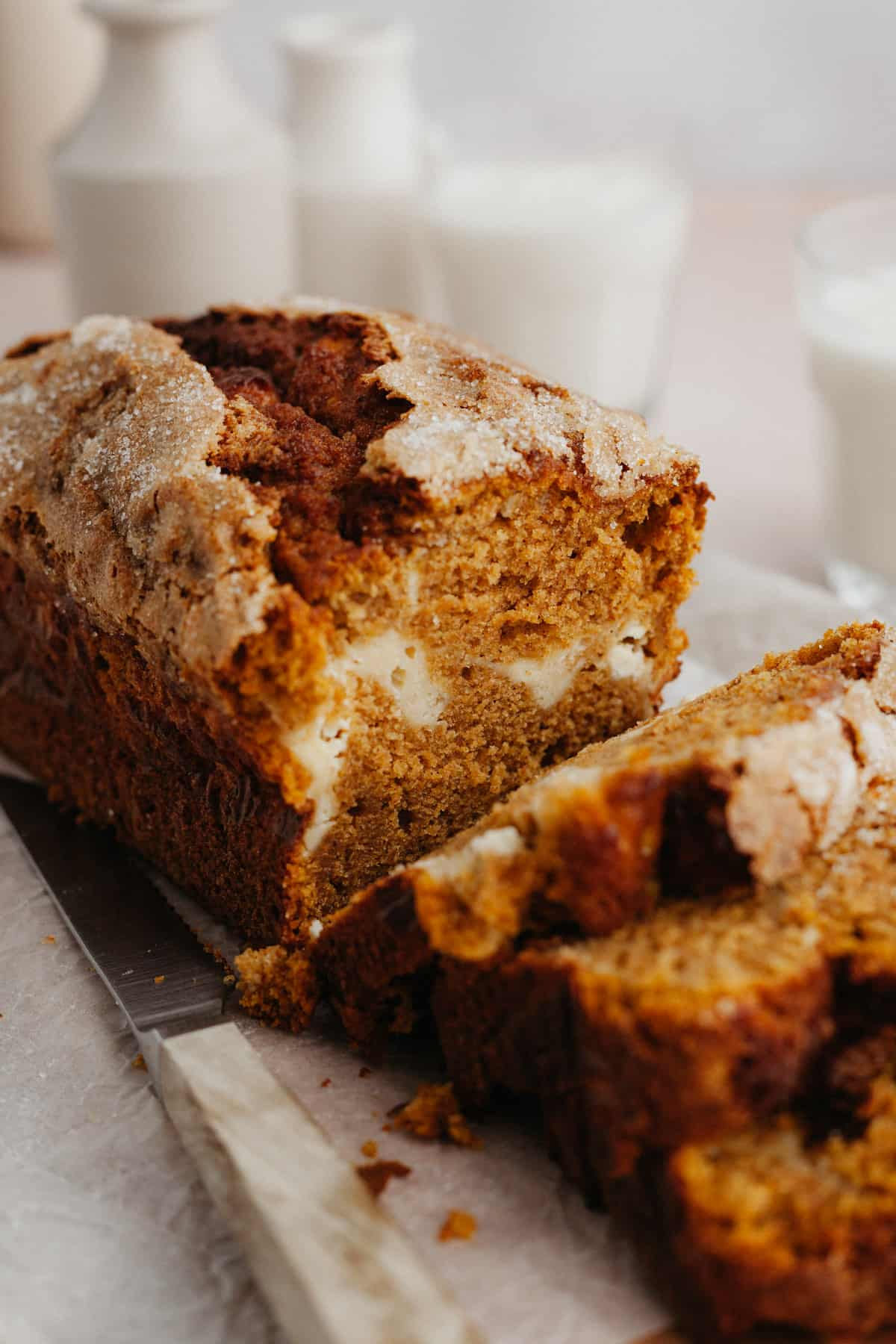A close up of a pumpkin bread loaf with several slices cut