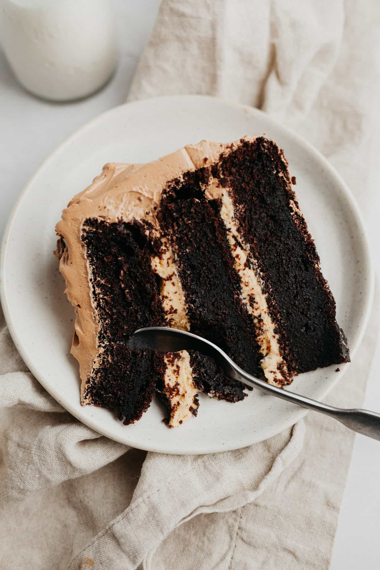 A slice of peanut butter and chocolate cake, made of three layers with a peanut butter filling, on a small beige plate.