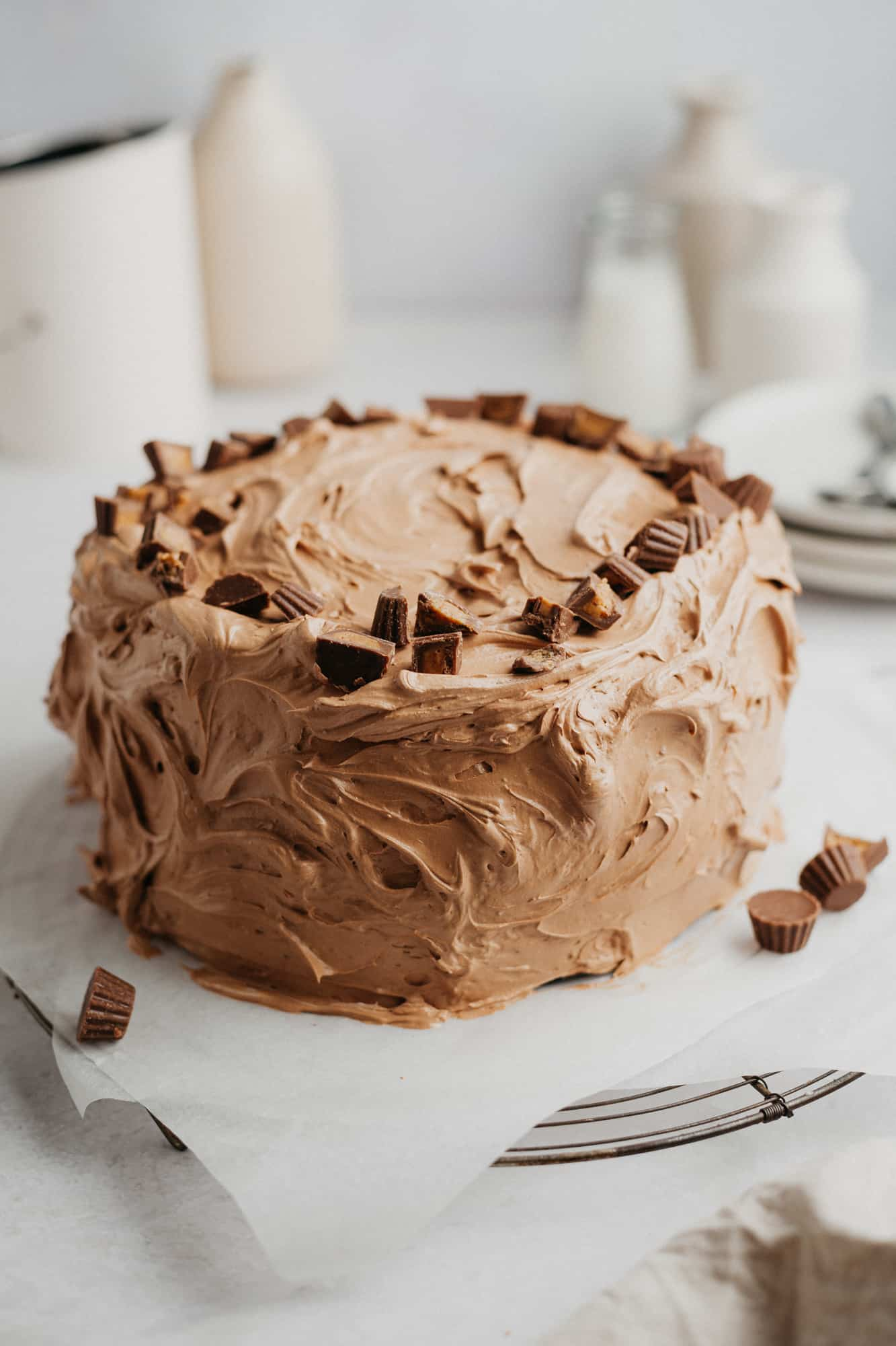 A chocolate cake with chocolate frosting. The top is covered in chopped miniature peanut butter cups. The cake is on parchment paper.