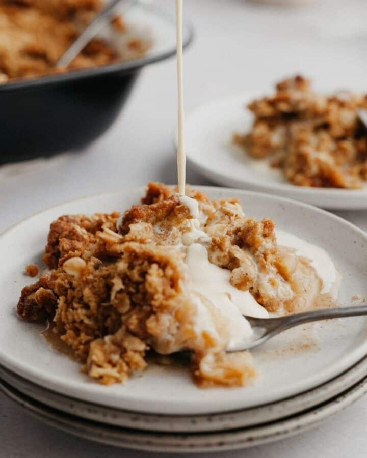 A plate of apple crumble with custard being poured on top