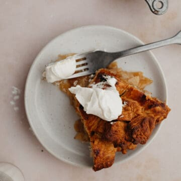 A slice of bourbon apple pie on a small plate. The pie has a dollop of whipped cream