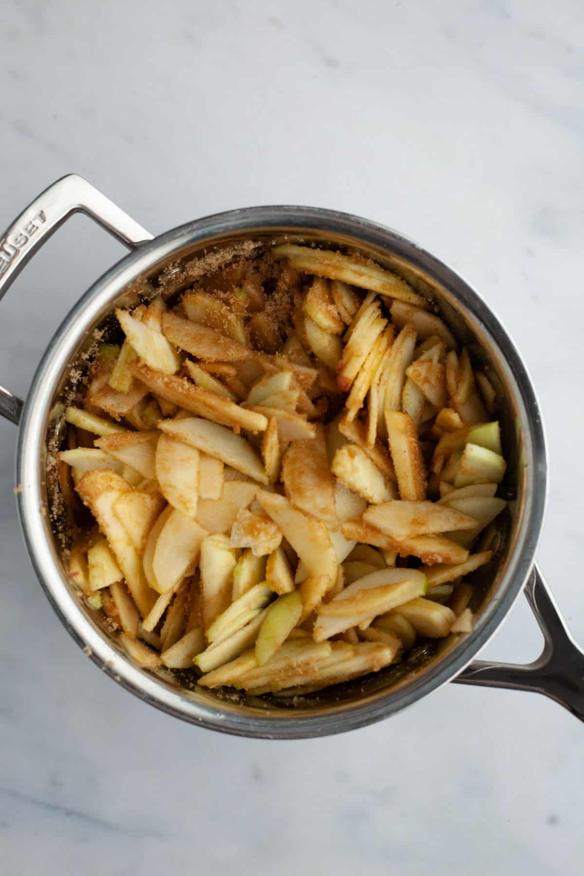 slices of apple tossed in cinnamon in a small saucepan