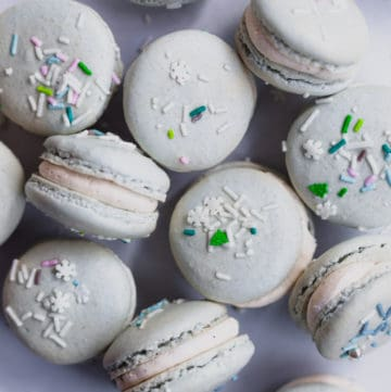 tin full of eggnog macarons with sprinkles on top
