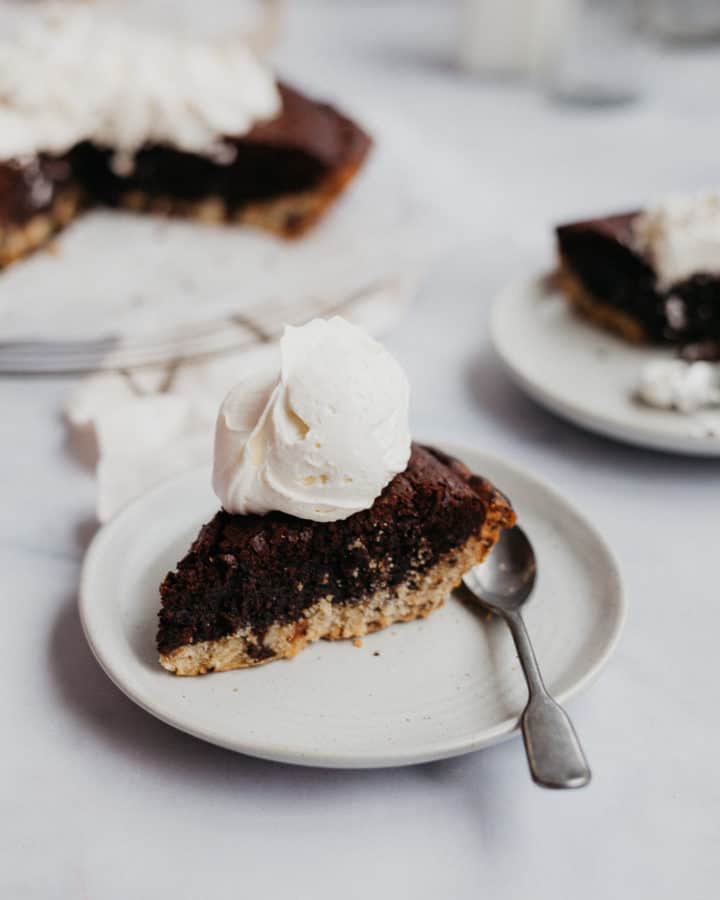 a slice of brookie pie with cream on top on a small plate