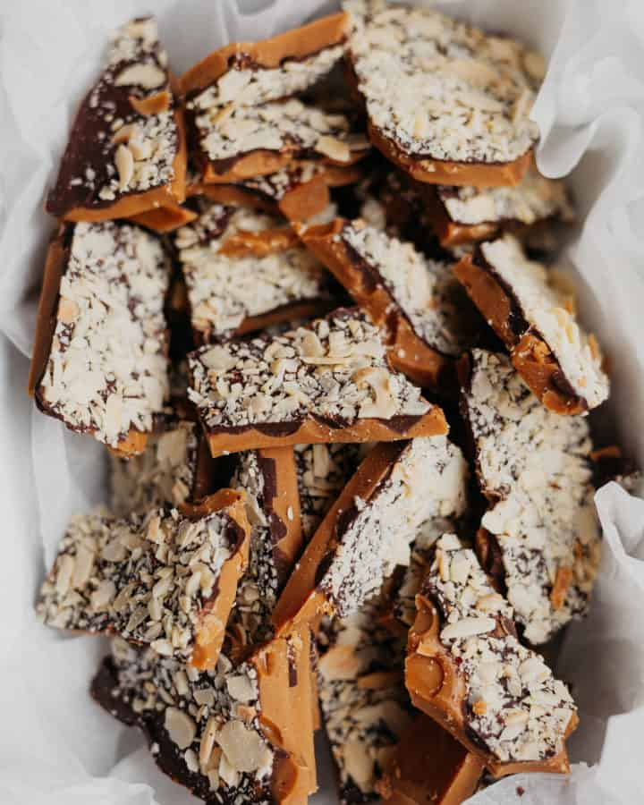 chopped pieces of almond toffee bark in parchment paper