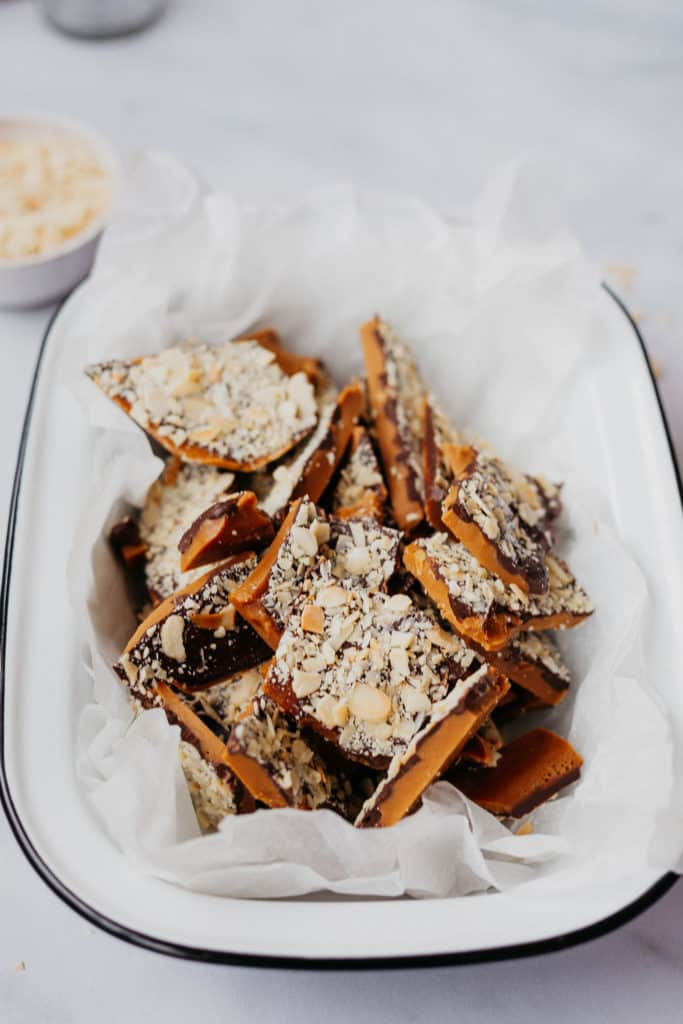chopped pieces of almond toffee park in an enamel tray