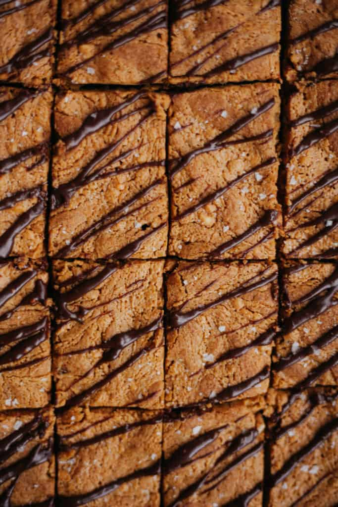 a close up of coffee peanut butter crunch blondies with mocha drizzle