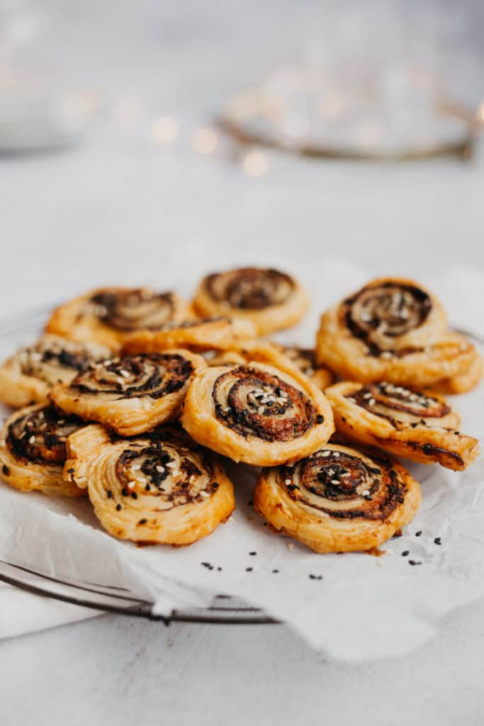 a pile of sesame and tapenade pinwheels on some parchment paper, fairy lights behind