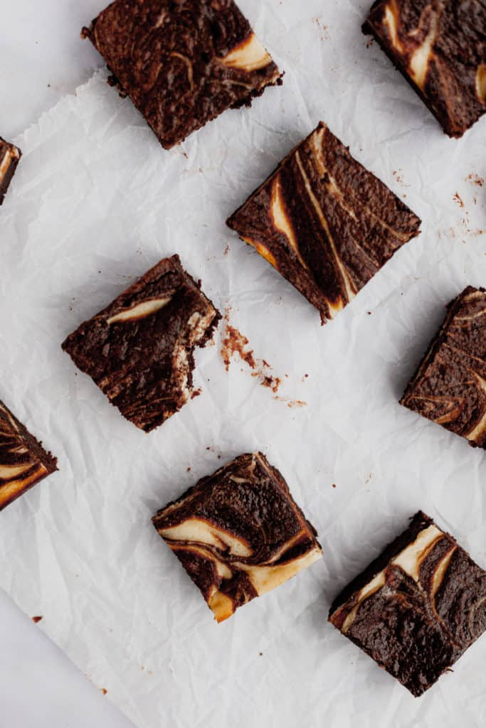 cut cheesecake brownies on parchment paper, one with a bite taken out