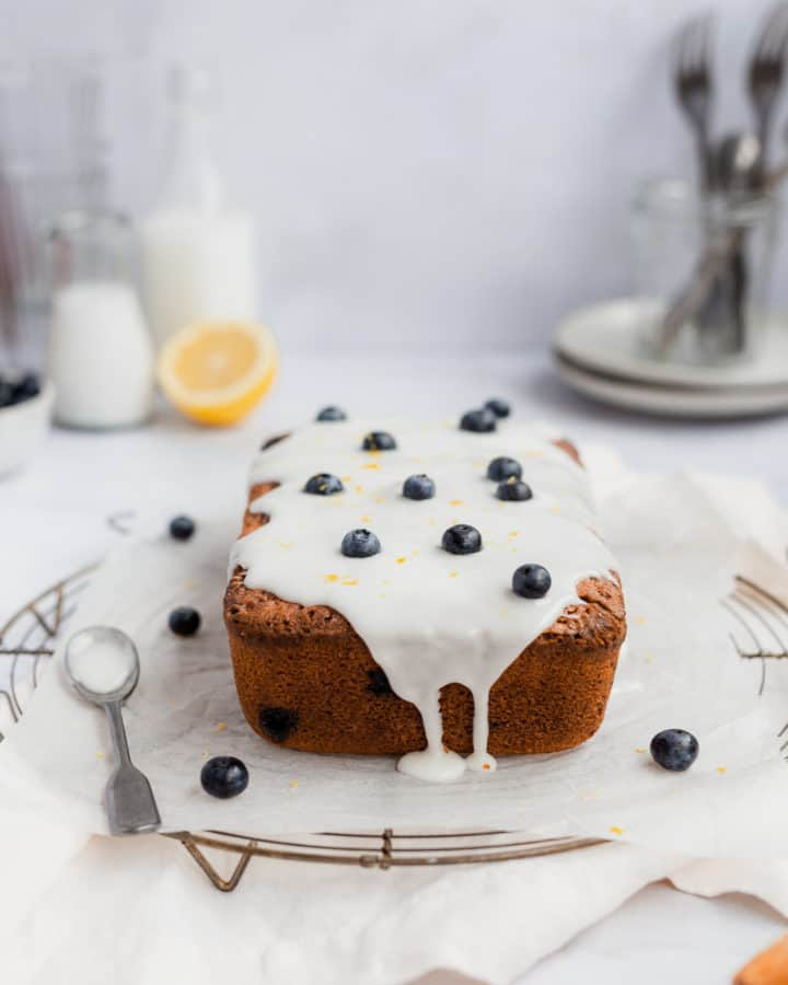 side view of a lemon pound cake with a drizzle, studded with blueberries