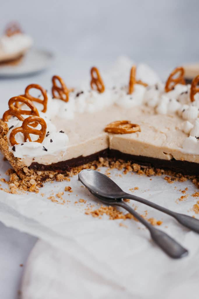 Side angle view of a butterscotch pie with a ganache bottom and pretzel crust
