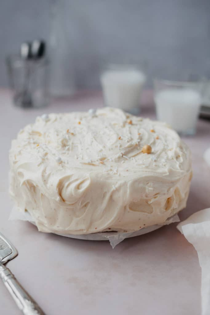 A cardamom cake frosted in cream cheese frosting with gold and white sprinkles on top. There are two small glasses of milk behind the cake