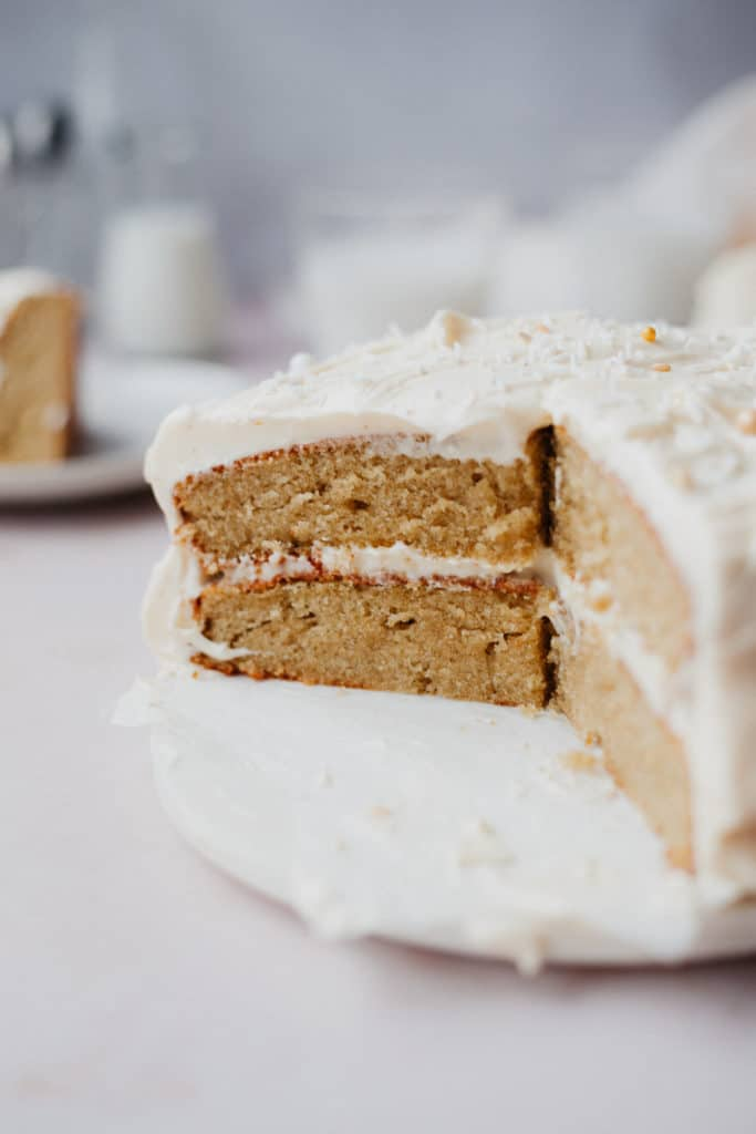 A cardamom cake with 1/4 of the cake taken out. It is a close up shot of the sliced cake