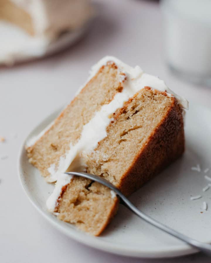 A close up of a slice of cardamom cake with a fluffy white frosting, a small spoon has taken one bite out