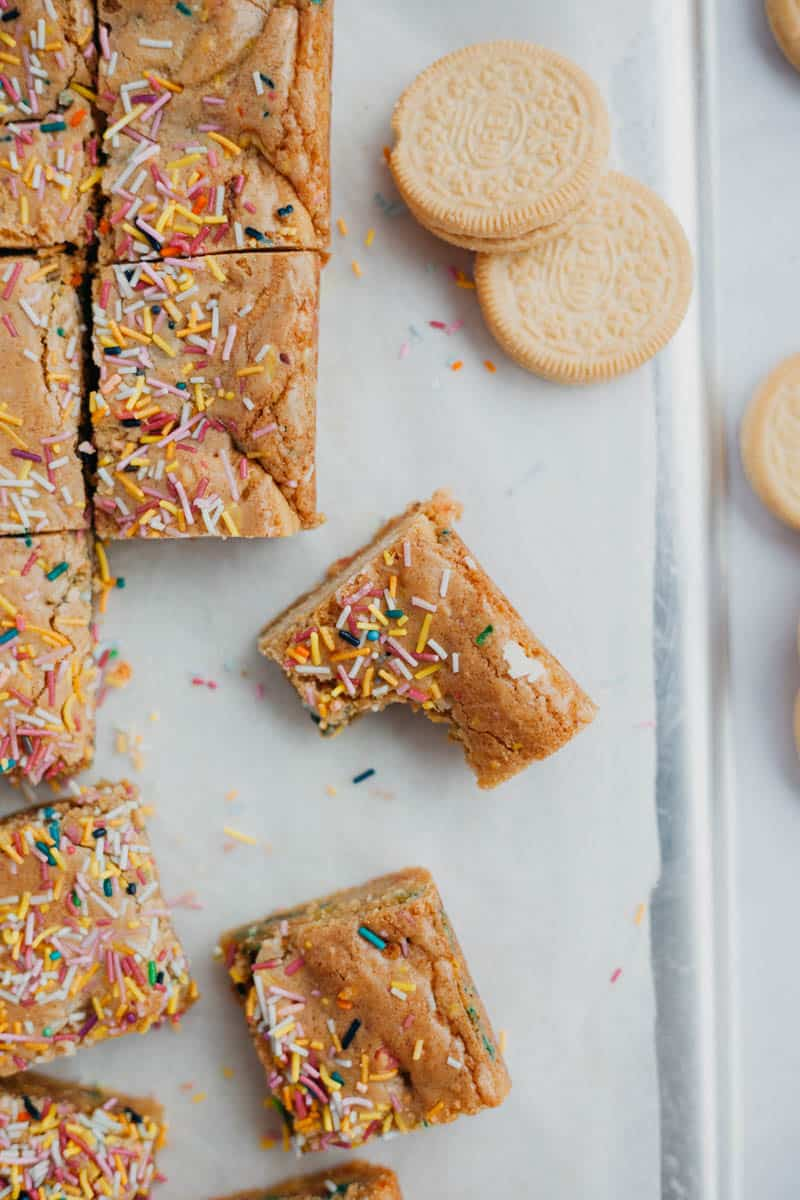 overhead shot of funfetti bars cut into squares, one with a bite taken out of it