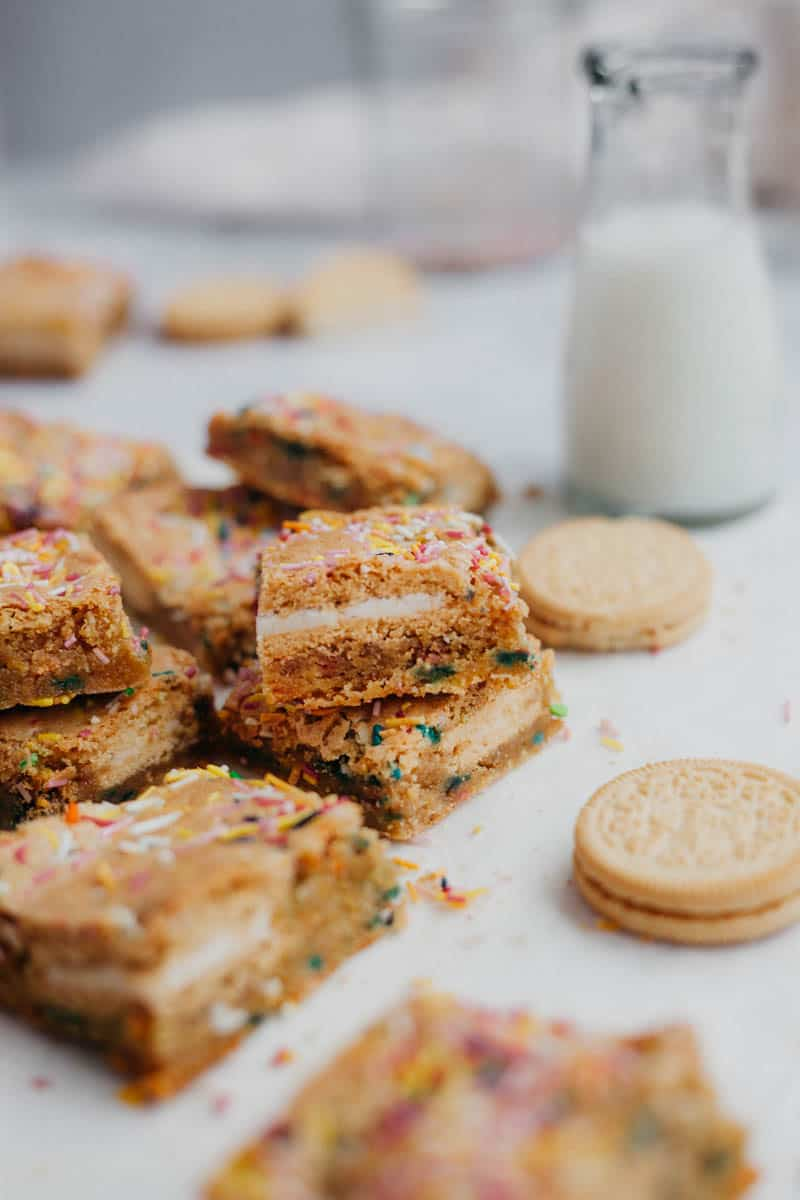 Funfetti bars stacked on top of each other, with a small bottle of milk