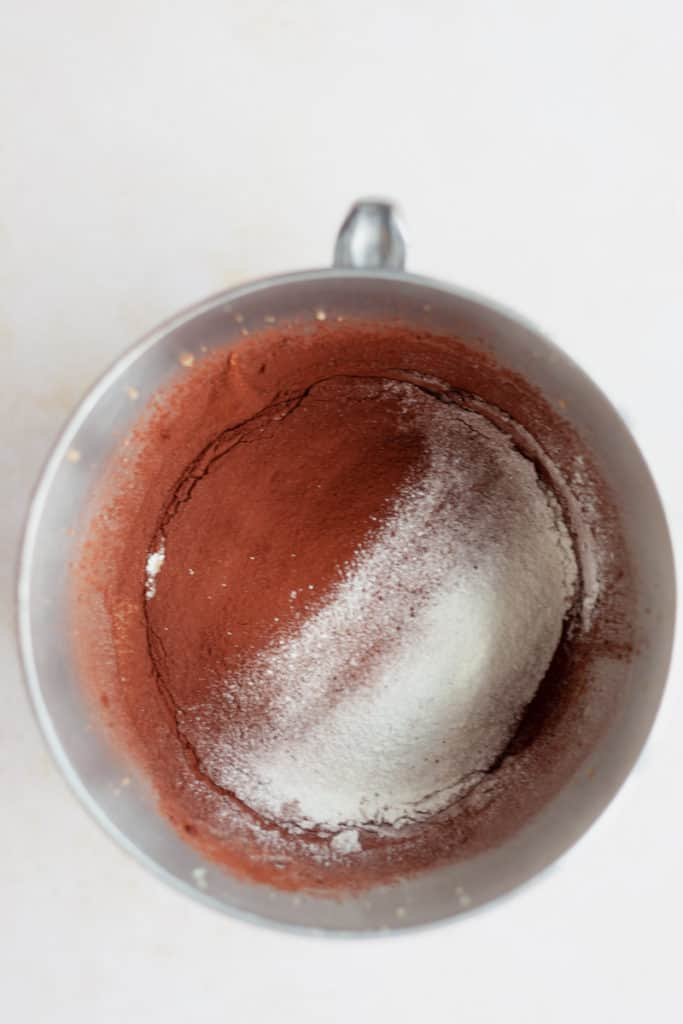 Overhead view of cocoa powder and flour in a large metal bowl