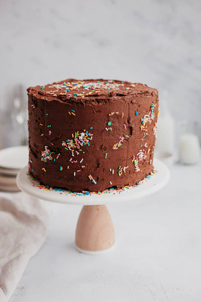A chocolate frosted cake with sprinkles on a cake stand