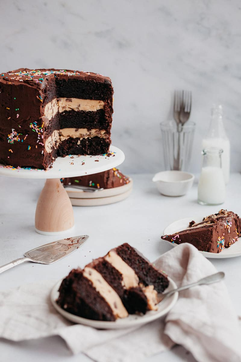 Chocolate cake on a cake stand with three slices on small plates