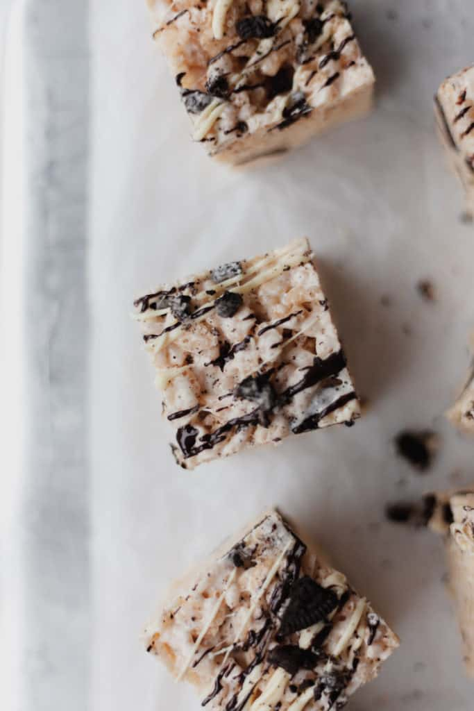 Overhead shot of 3 rice krispie squares, drizzled with chocolate