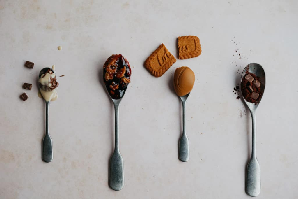 Four spoons in a row, one with cocoa powder, one with biscoff cookie butter, one with peanut butter and jelly, and one with nutella and tahini