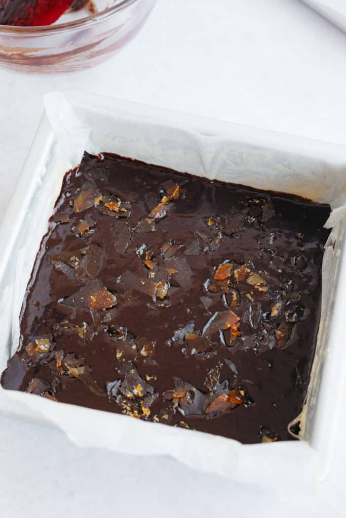An 8x8 baking tin with unbaked brownie batter and caramel shards sprinkled on top