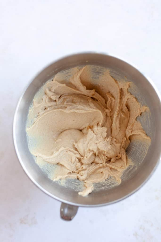 An overhead shot of cookie dough in a large metal mixing bowl