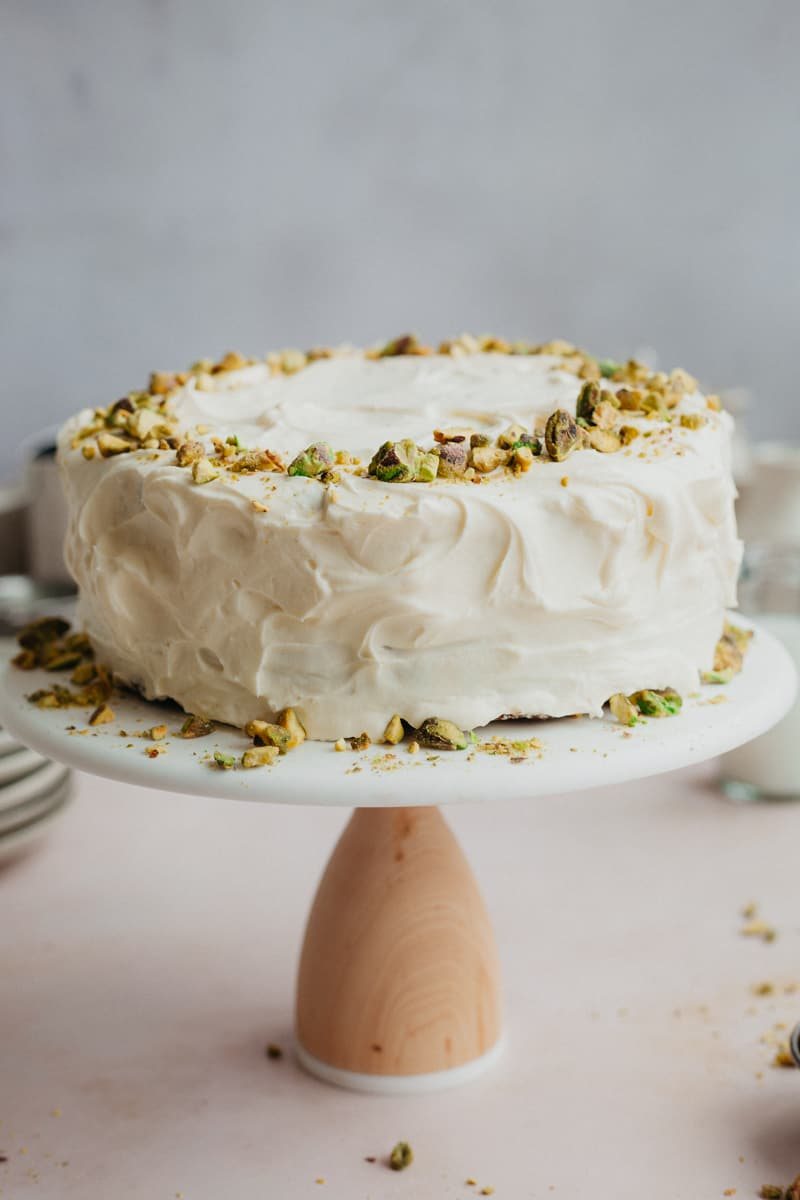 A frosted cake decorated with pistachios on a white and wooden cake stand.