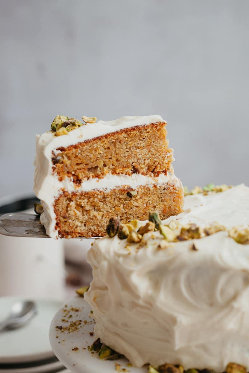 A close up of a slice of carrot cake being lifted.