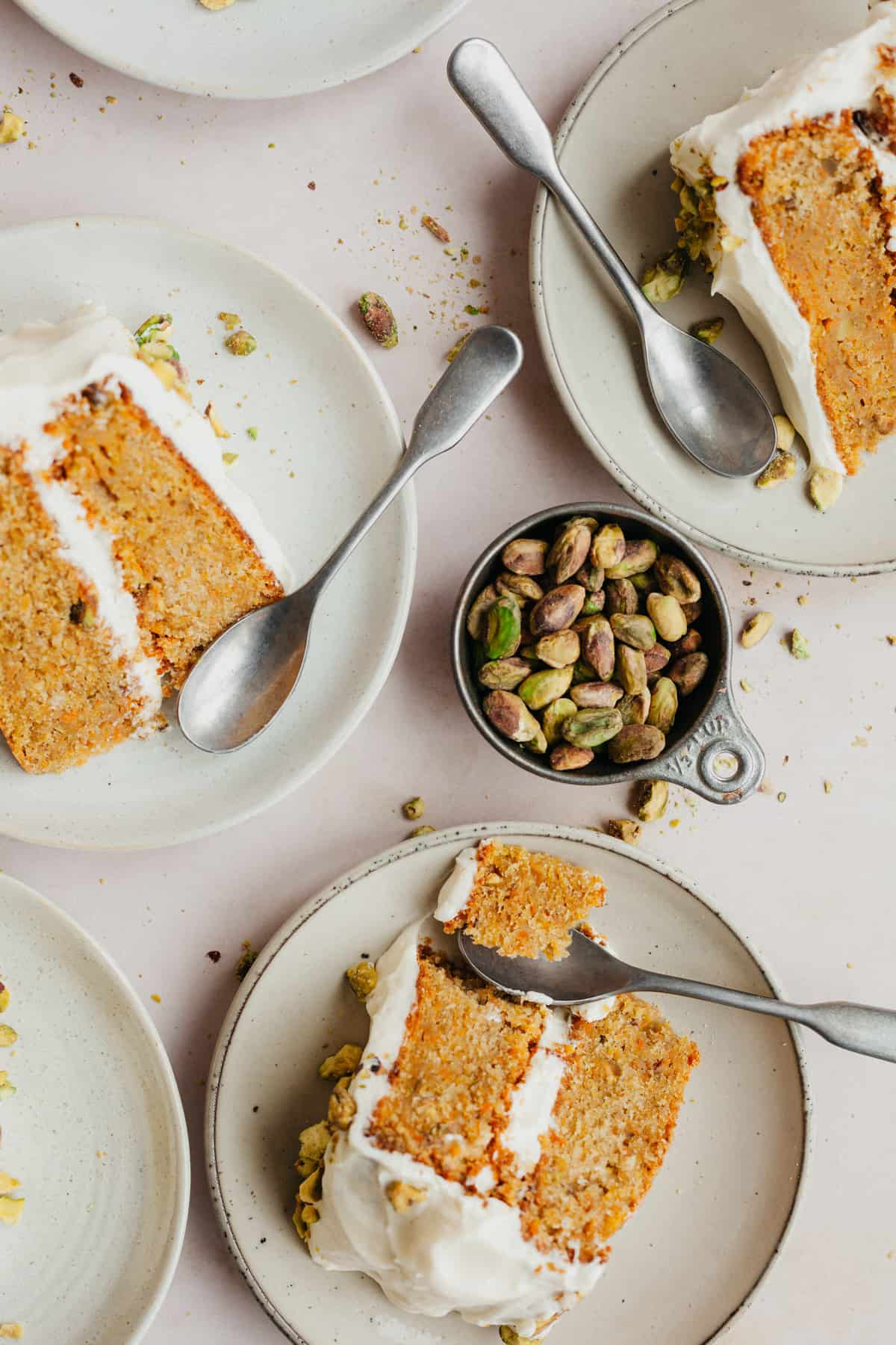 Three small plates with slices of carrot cake on each plate and a small spoon. There is a metal measuring cup filled with pistachios.
