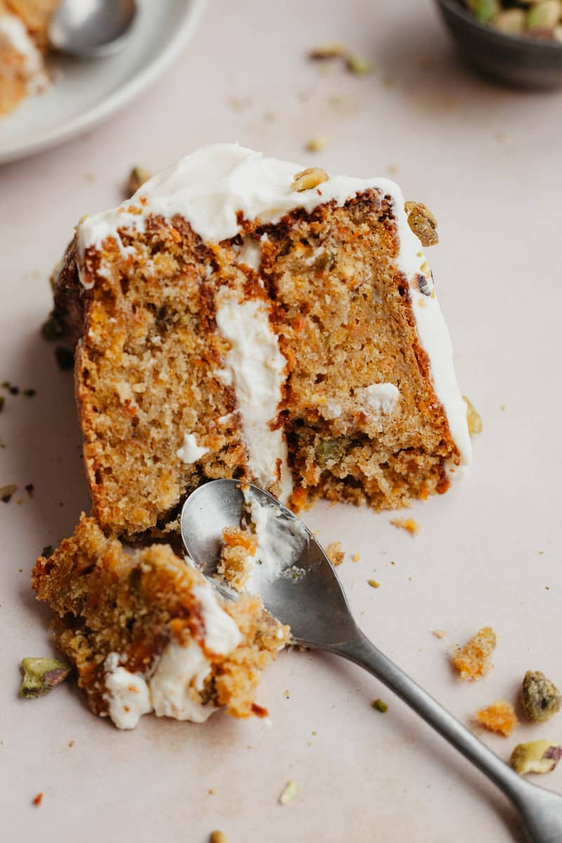 A slice of layered carrot cake with a small spoon scooping out a piece