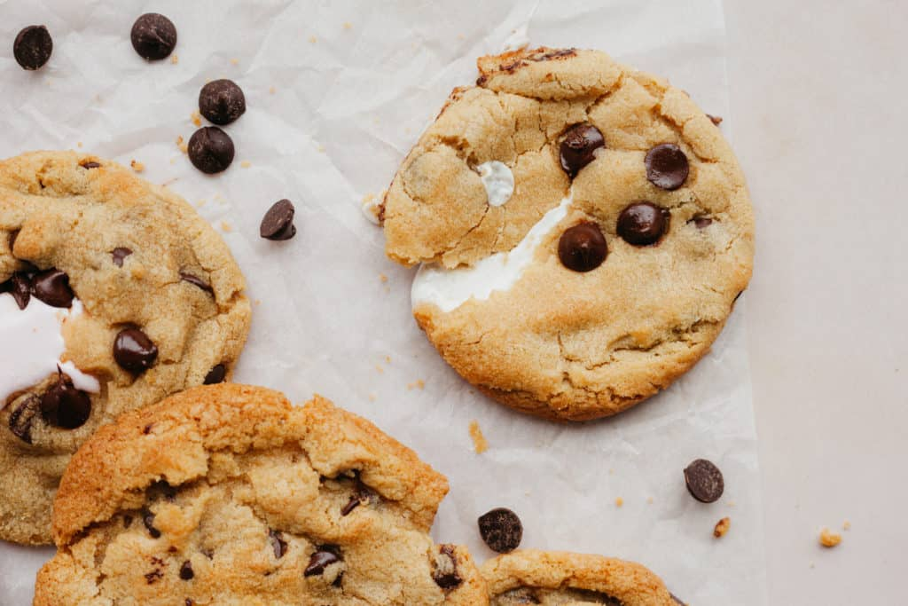 A close up of three chocolate chip cookies with a marshmallow middle on parchment paper