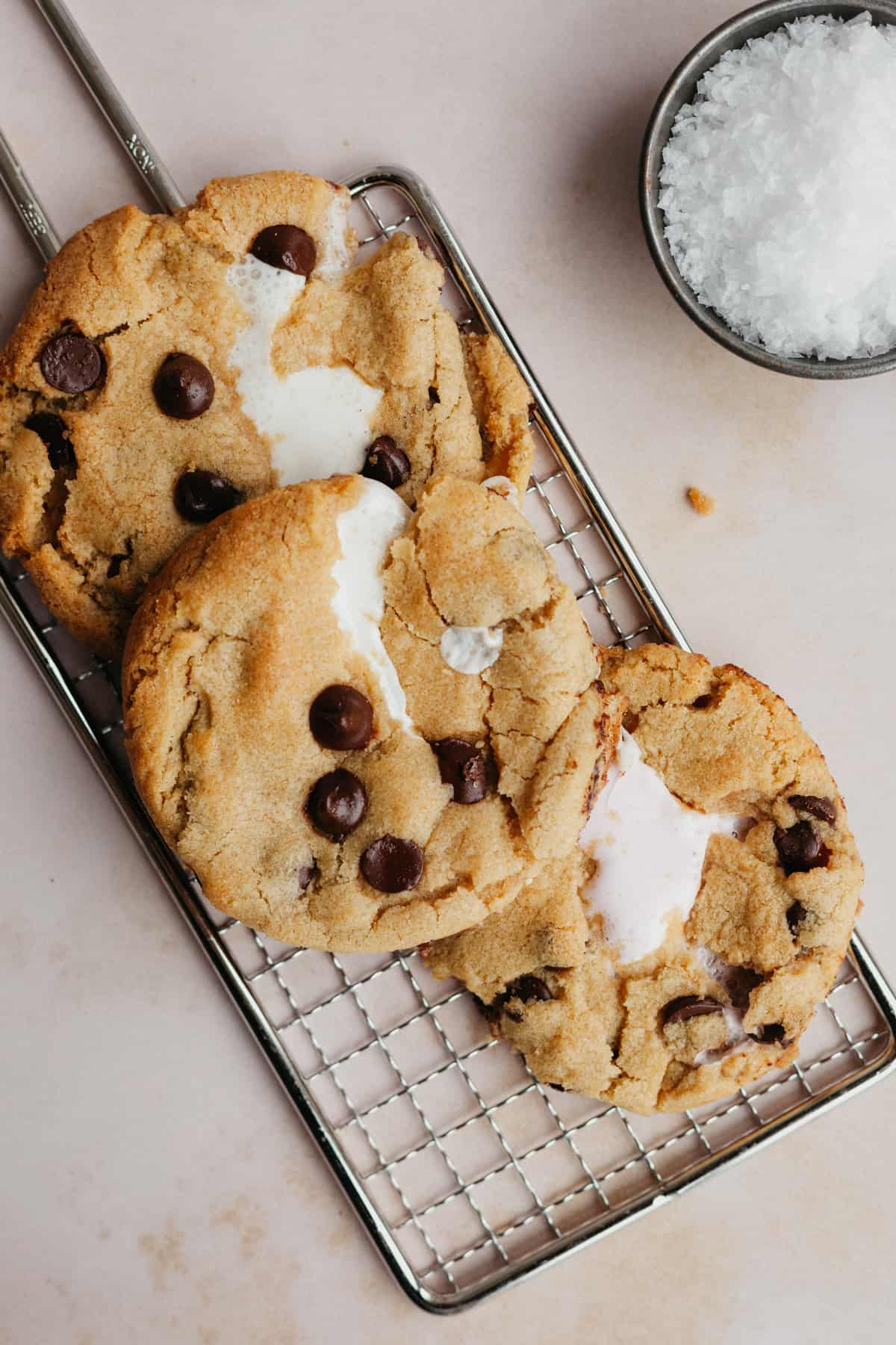 Three marshmallow chocolate chip cookies on a small rectangular cooling rack