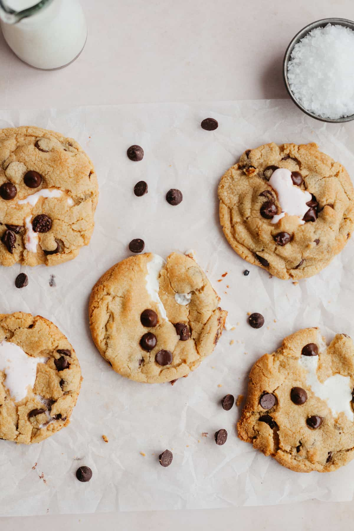 Five marshmallow chocolate chip cookies on parchment paper with some chocolate chips scattered around and a small bottle of milk
