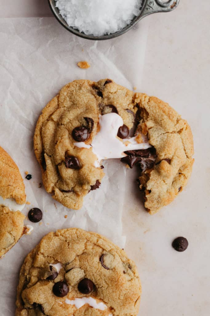 Two chocolate chip cookies on parchment paper. One is being pulled apart and you can see it has a marshmallow centre