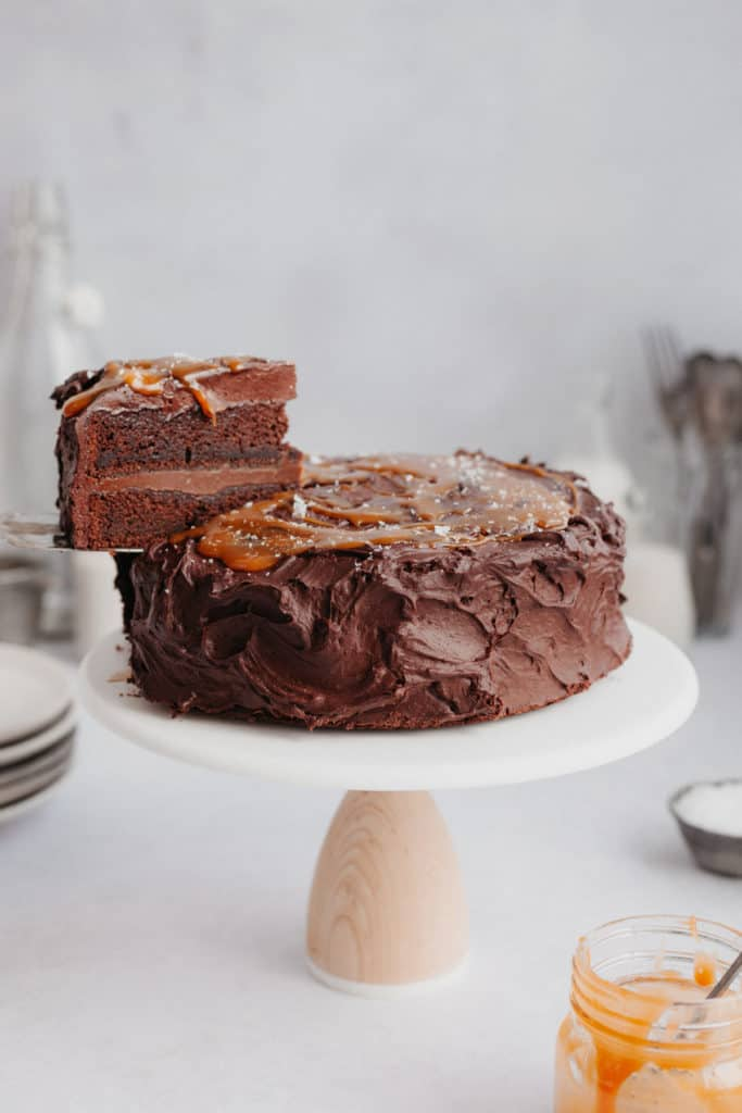 A chocolate cake with a caramel topping on a cake stand. One slice is being lifted out