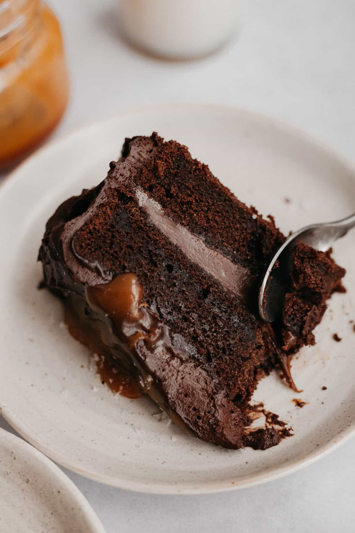 A salted caramel chocolate cake slice on a small beige plate