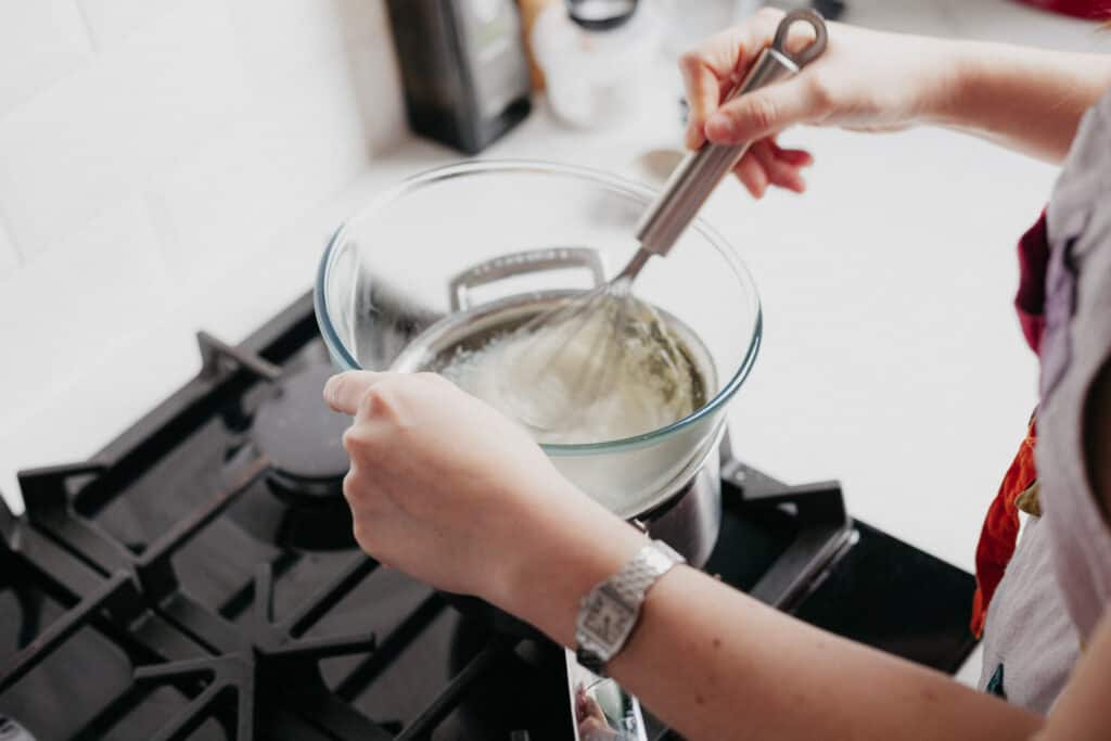 A pyrex bowl over a double boiler. The bowl has egg whites and sugar, and Ella is whisking it together.