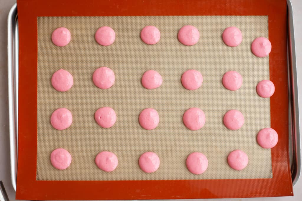 A baking tray with a silpat baking mat and piped out pink macaron shells, unbaked