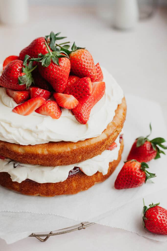 A strawberry filled cake on parchment paper