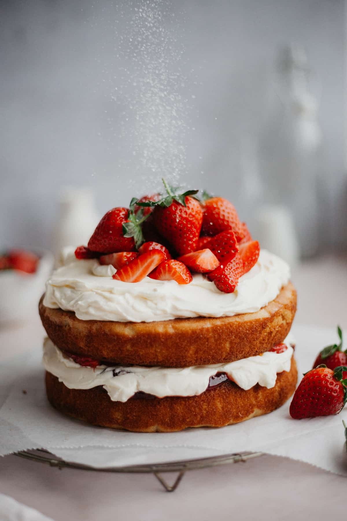 A naked cake, with a whipped cream filling and topping, topped with strawberries. There is a light shower of powdered sugar coming down.