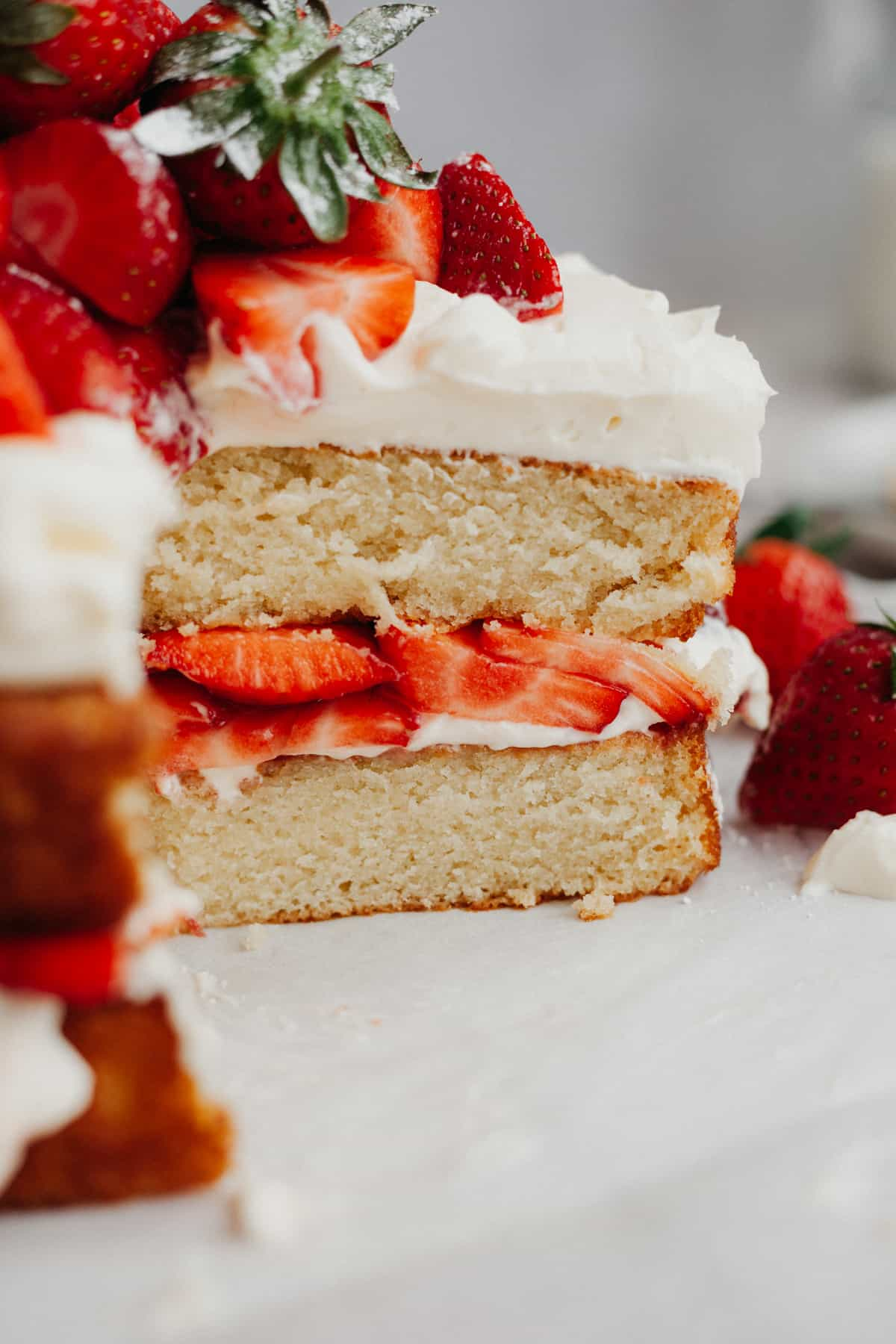 A close up of a strawberry filled cake that has had several slices taken out
