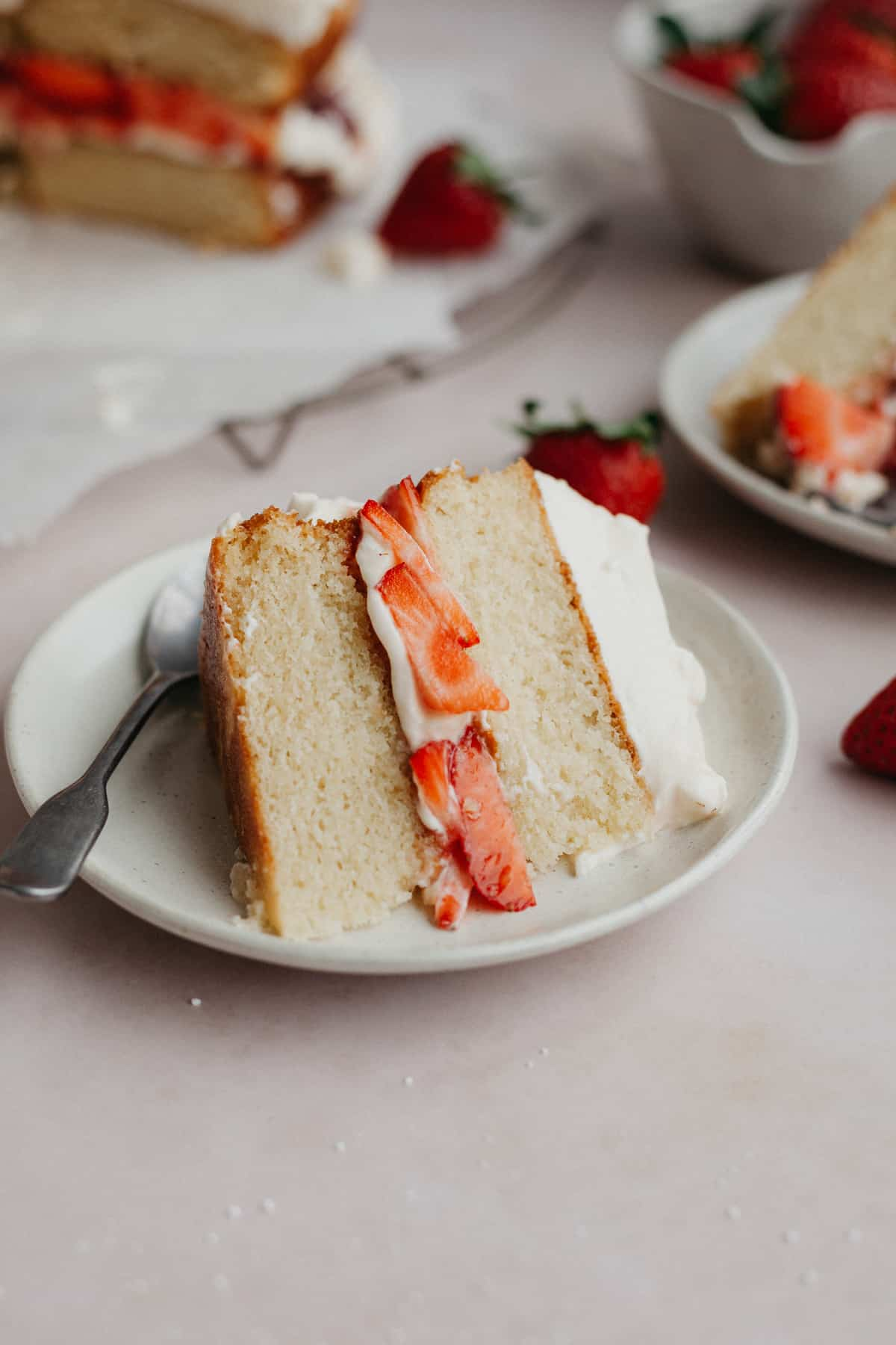 A slice of white cake that has a strawberry filling, on a small beige plate