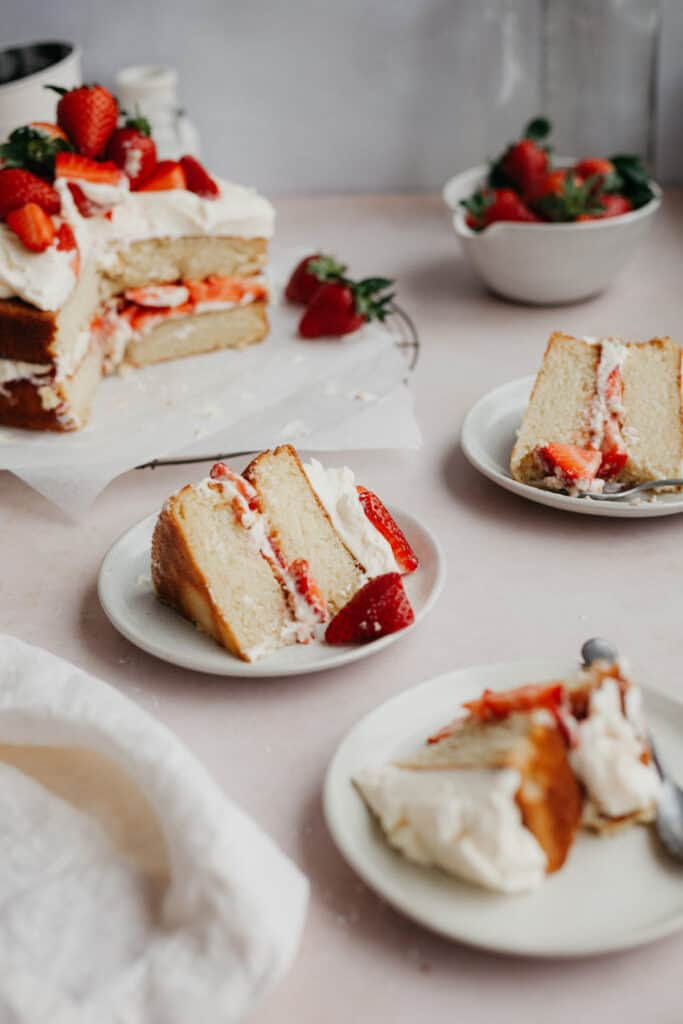 Three slices of white cake with strawberry filling on small beige plates.