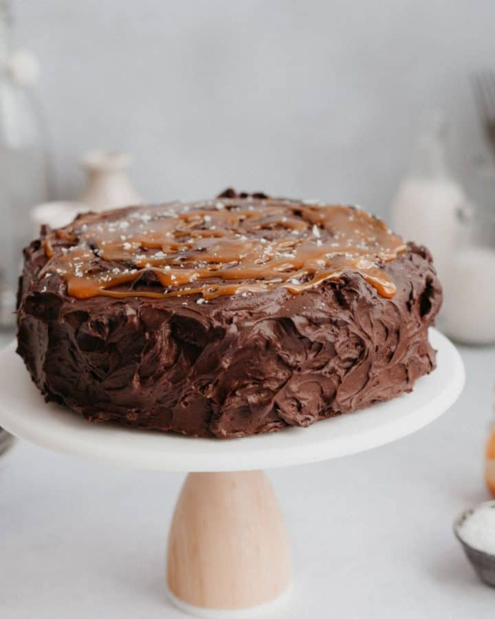 A salted caramel chocolate fudge cake on a white and wooden cake stand