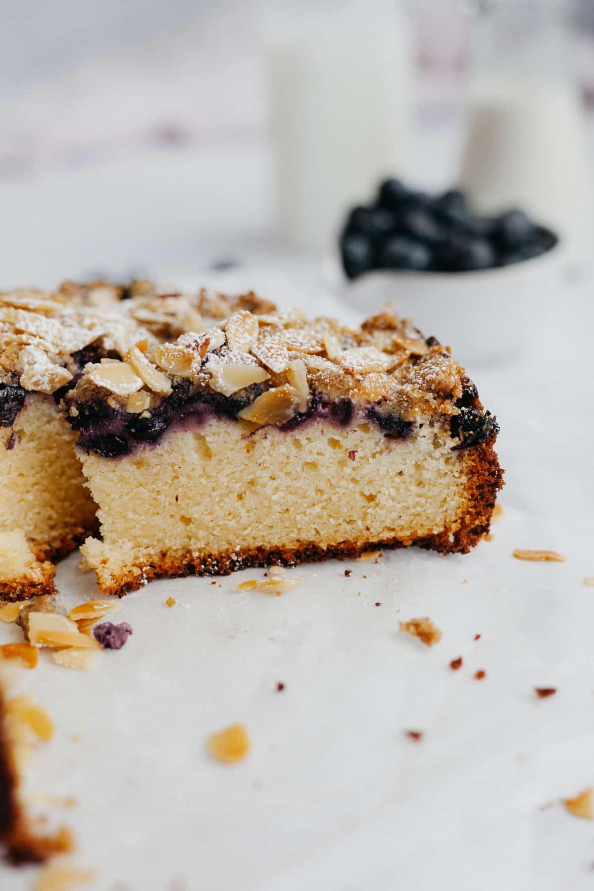 A side angle shot of a slice of blueberry almond lemon cake.