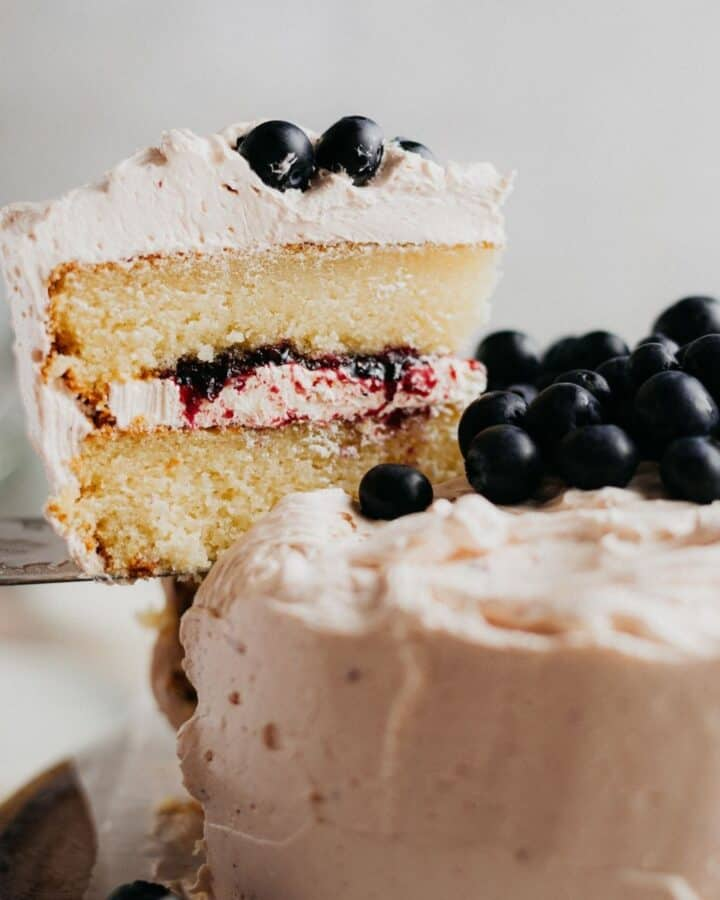 A slice of blueberry jam cake being lifted out with a silver cake server